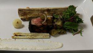 Contre-filets de bœuf grillés, os à moelle, raisins, jus de viande et salade d'herbes