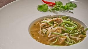 Soupe au poulet aigre et épicée parfumée à l'ail
